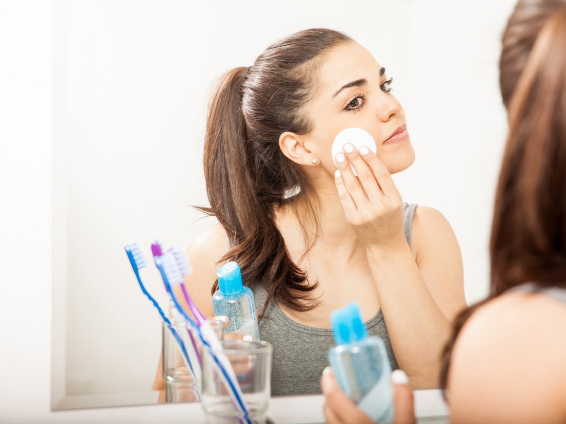 Portrait of a beautiful young brunette using a cotton pad to remove her makeup in the bathroom at night